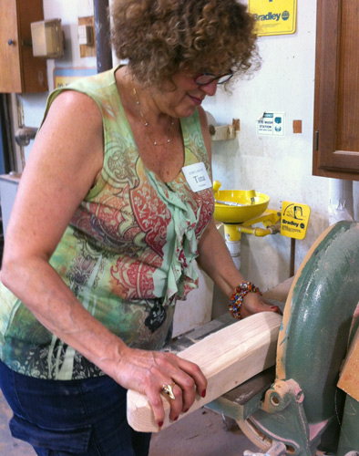 Tina disk-sands the corners off the chain-sawn block of ash we chose for shoulders. She did not like the dust.