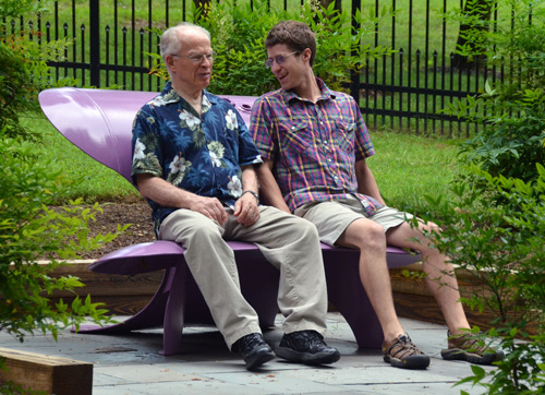 Phil Brown and Ben Carpenter take a test sit on a purple bench made from a steel propane tank by the California artist Colin Selig.