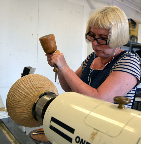 Gaynor Dowling tries using the lathe as a holding device while she carves the exterior of a bowl that Ben turned.