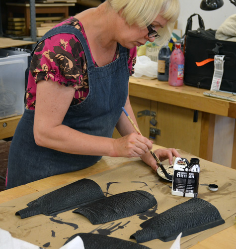 Gaynor paints the carved bottle halves with black dye. It dematerializes the wood figure, leaving only the carved texture.