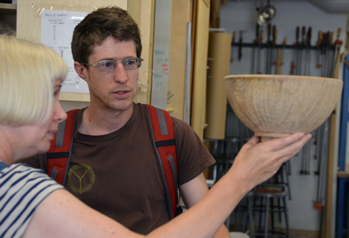 Gaynor Dowling shows Ben Carpenter the result of her carving on his turned bowl.
