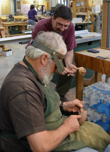 Keith Holt and Norm Sartorius chat together while working on hand-held carvings with hand-held rasps, files,and sandpaper.