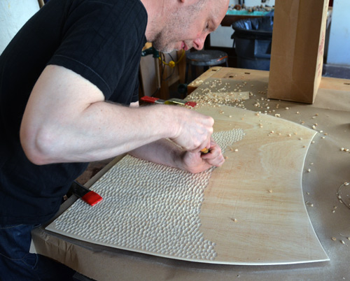 Malcolm patiently textures the bending plywood, one chip at a time.