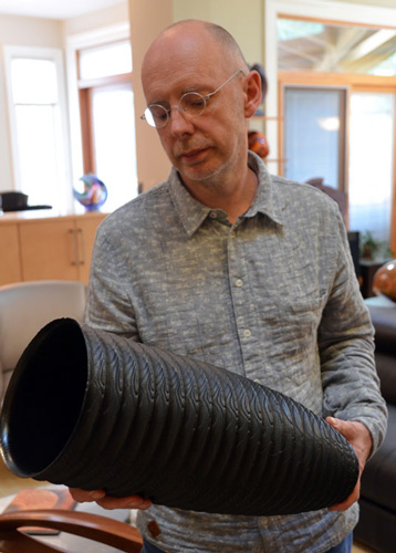 Malcolm examines the carved and blackened surface of this tall vessel in the Bernstein collection.