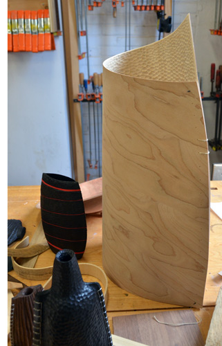 The shot you've been waiting for: Malcolm's bending-plywood bottle form tacked together, waiting to be sewn. He says the texturing didn't affect how it bends. I'm surprised the texture is on the inside. Not to worry, he replies, there's another one on the way with carving on the outside.