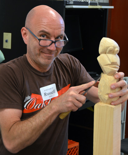 Russell Baldon, head of the furniture program at California College of the Arts in San Francisco, carves a face on the collaborative community totem pole.