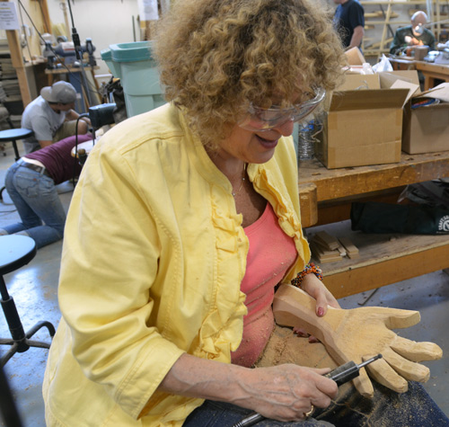 Tina Fruchter tries power carving using Keith Holt's Foredom set-up. Keith bandsawed the hand, Tina is shaping it.
