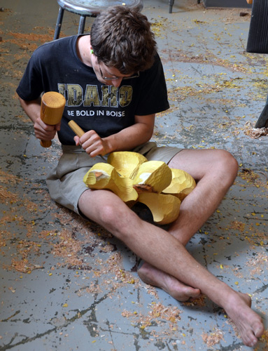 Ben sits to carve an osage orange sculpture. We all wish the yellow color would persist even as we know it will go brown soon.