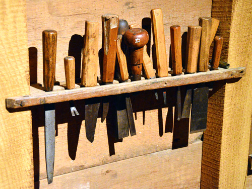 A wall rack of chisels and carving tools, all with shop-made handles on forged blades.