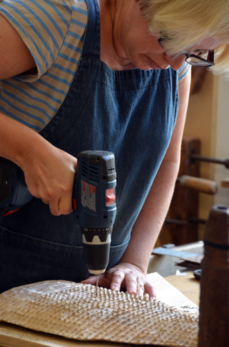 Gaynor Dowling drills tiny holes into the much-carved oak monolith. She pl;ans to dye the wood black, and stitch red-orange thread into the holes.