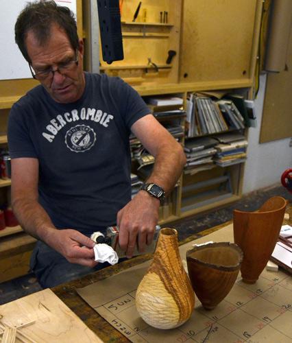 Neil Turner wipes polyurethane varnish onto three turned-and-carved vessels.