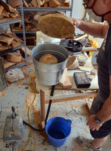 neil's steam-bending setup. The piece is in the galvanized bucket, with steam entering via the black hose. It doesn't take a long time to soften the ash wood.