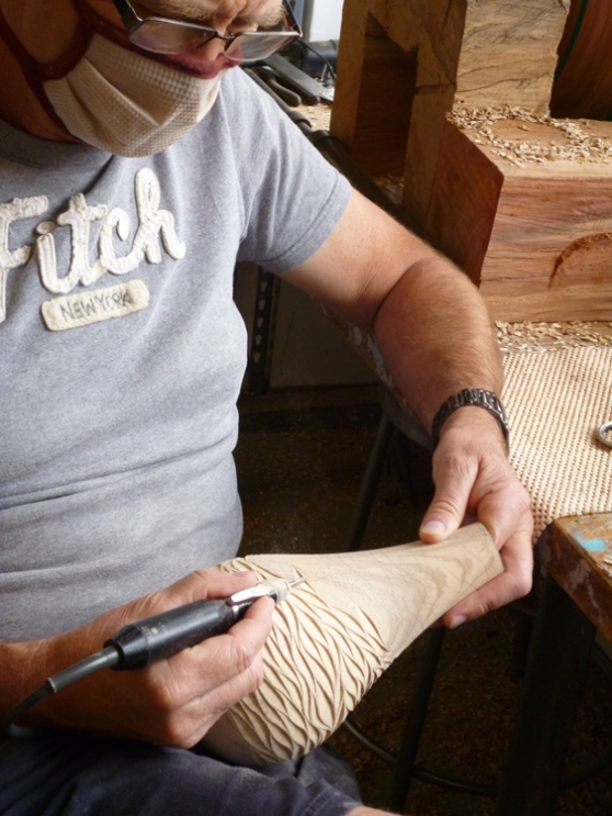 Meanwhile, puffs of wood-dust from Neil's carving tool, as he creates the surface on this vessel...
