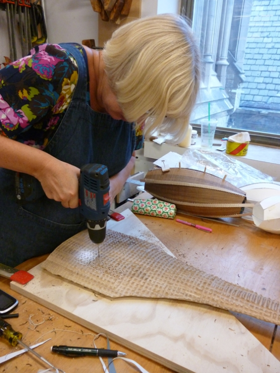 Gaynor drills holes into a carved piece, looks like there's more stitching on the way..