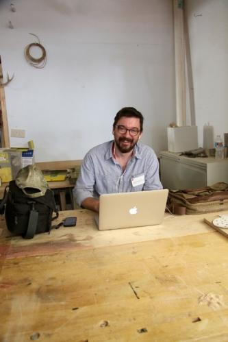 ITE Scholar Fellow, Seth Bruggeman, works on his blog postings as the Open studio activities convene around him.